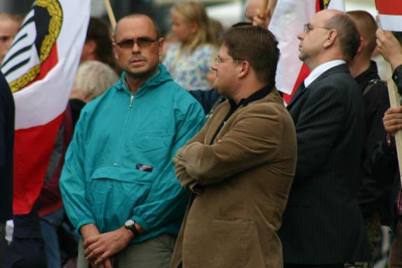 Rocco Kilz (in türkis) als Personenschützer des ehemaligen NPD-Fraktionsvorsitzenden in Sachsen Holger Apfel (Mitte) zusammen mit damaligen NPD-Vize Peter Marx (rechts) am 15. August 2005 auf einer Kundgebung in Dresden.
